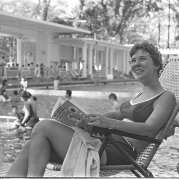 Black-and-white photo of a woman sitting in a pool chair with a magazine by a swimming pool