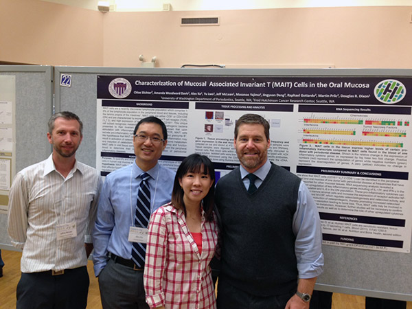 Dr. Jeffrey McLean, Dr. Alex Ko, Dr. Ruby Lwo and Dr. Douglas Dixo stand in front of their research poster. Drs. Dixon and McLean were Co-PIs on the poster.