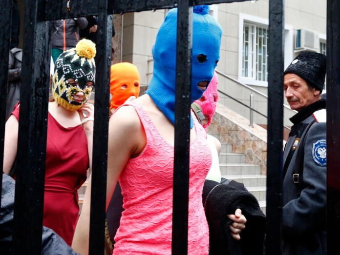 Masked members of protest band Pussy Riot leave a police station in Adler during the 2014 Sochi Winter Olympics, February 18, 2014. Two members of Pussy Riot, Maria Alyokhina and Nadezhda Tolokonnikova were detained on Tuesday in connection with a theft in the Winter Olympics host city of Sochi, less than two months after their release from prison under an amnesty.         REUTERS/Shamil Zhumatov
