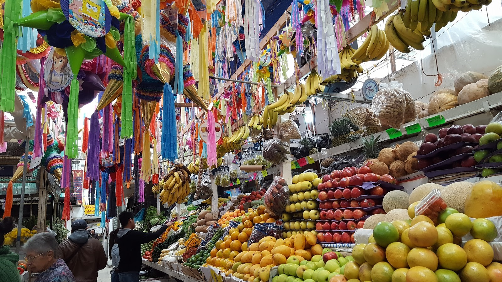 Photograph of market stall filled with bright fabrics and fruit and veg