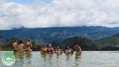 A group of students in a hotspring with mountains in the background