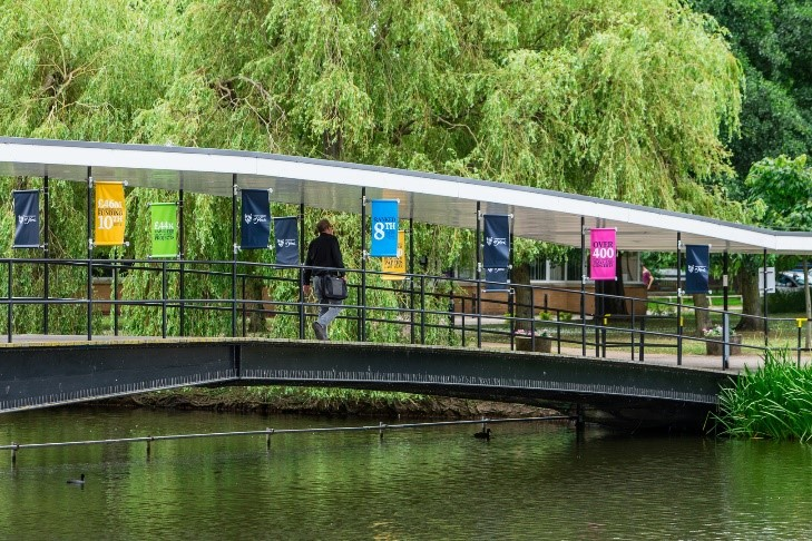 A view of the University of York's campus lake showing a man walking across the bridge near Central Hall.