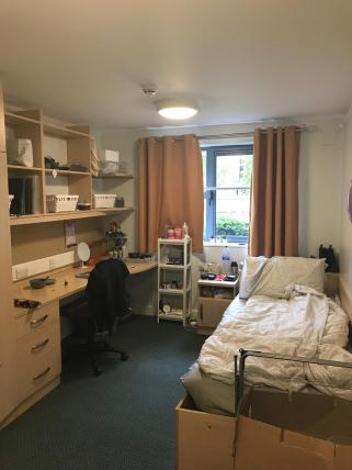 Inside of a student bedroom in Vanbrugh College. There is a single bed, a desk and chair with shelving above the desk.