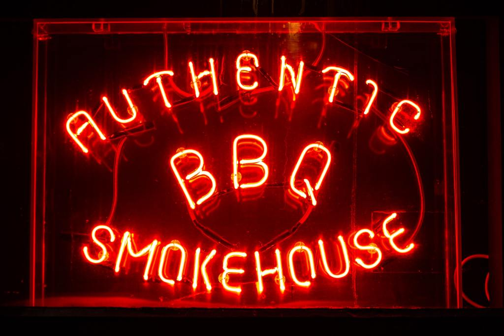 Neon sign in the Pavement Vaults restaurant in York which reads authentic BBQ smokehouse