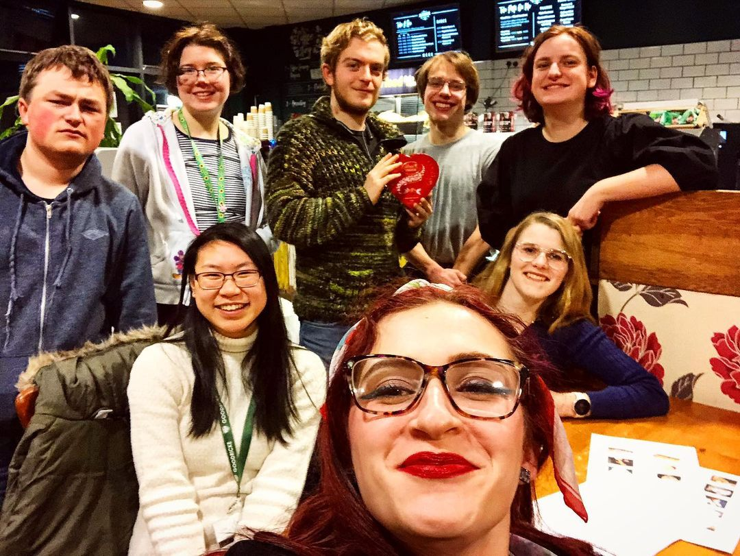 An image of Amy (bottom middle) at the Kitchen in Alcuin after the Sober Society 'Quiz in the Kitchen'. 7 students of varying backgrounds and genders sit or stand around Amy, the one in the top middle (a white male) holds some chocolates he won from the quiz.