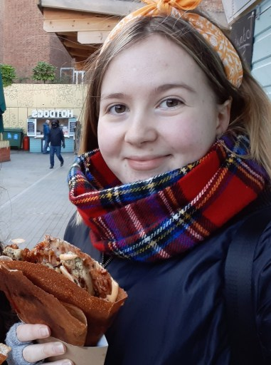A picture of student Caitlyn sat outside holding a crepe