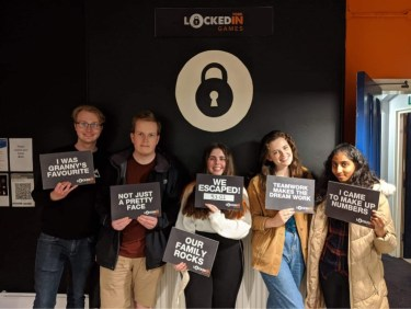 Five students stood after completely an Escape Room