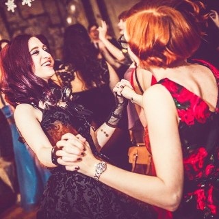 Me at the 2018 Archaeology Society Winter Ball. I'm wearing a black dress and have shoulder-length purple hair, I have steampunk style goggles around my neck. I am holding hands and dancing with someone with their back to the camera in a red dress with close-cropped orange hair. I am smiling and look like I'm enjoying myself. There are also people dancing in the background.