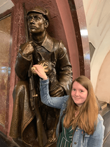 A female student standing with her hand on a bronze statue of a solider in Moscow