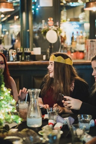 A female student sitting at a table during a party wearing a Christmas paper hat and smiling