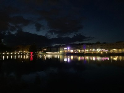 Looking over a lake at night showing the lights glowing from different buildings