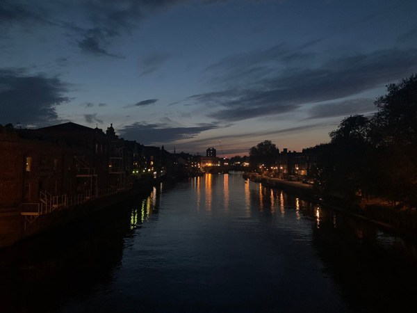 The River Ouse in the city of York at night. There are lights reflected on the water.