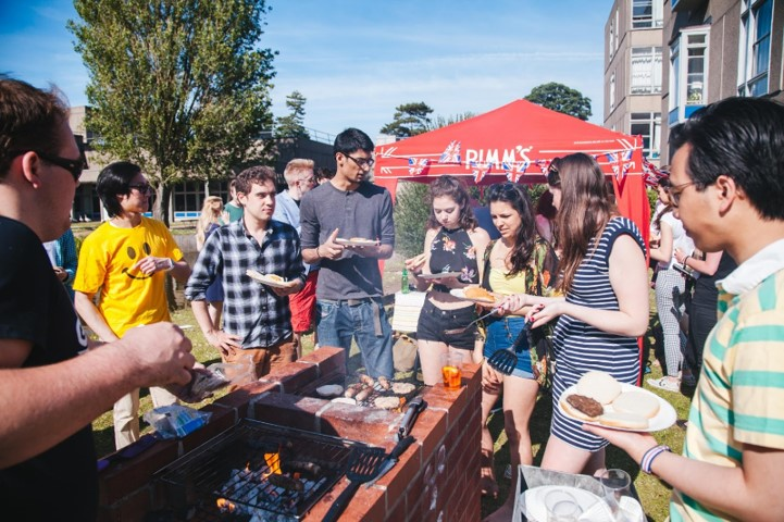 A group of students outside on a sunny day having a BBQ together
