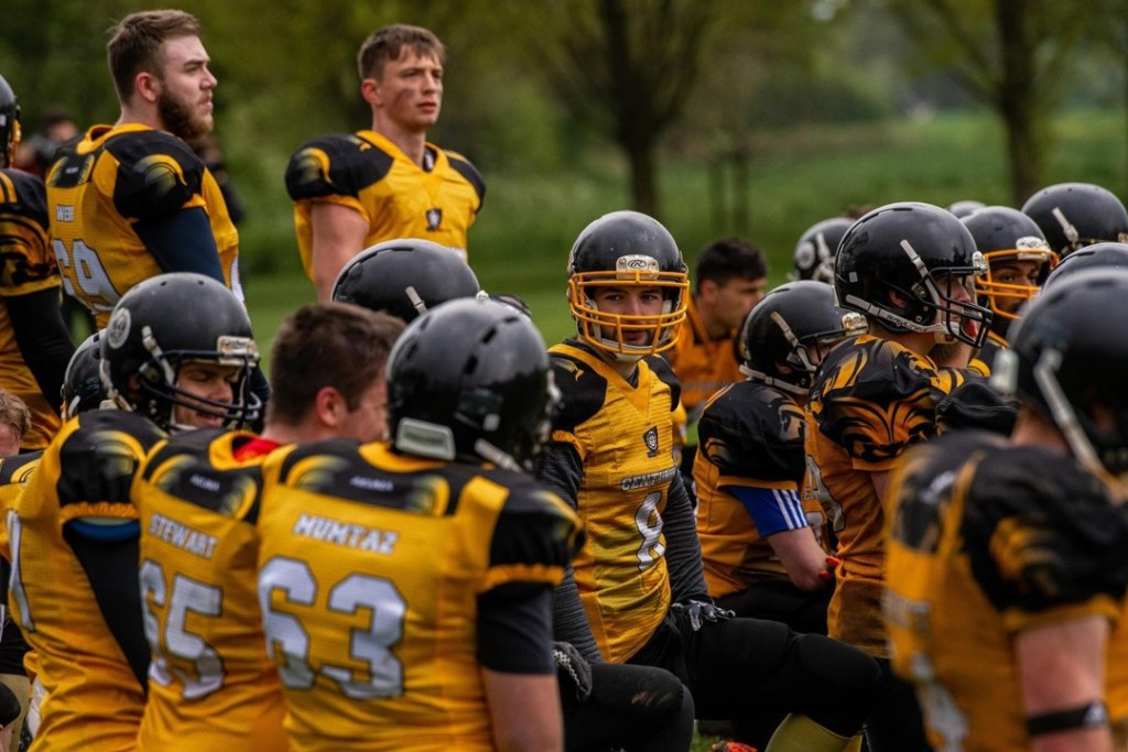 A group of American Football players wearing the Uni of York kit waiting to play