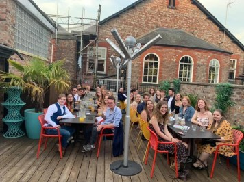 A group of Nouse students sat round two big tables outside at a social event