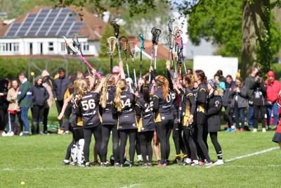 A female lacrosse team huddled together celebrating after winning a match.