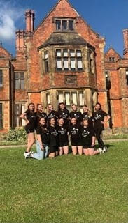 A group of 12 female students grouped together for a photograph outside Heslington Hall on the University of York campus. All the students wear black tops.