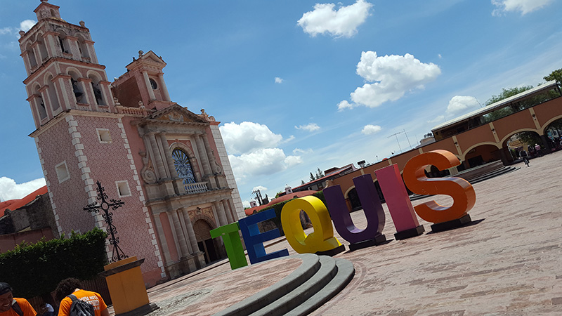 A historical building with large colour letters outside which spell TEQUIS in the town of Tequisquiapan, Mexico