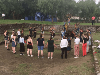 A group of people stood around in a circle outside. They're taking part in a traditional Mexican dance