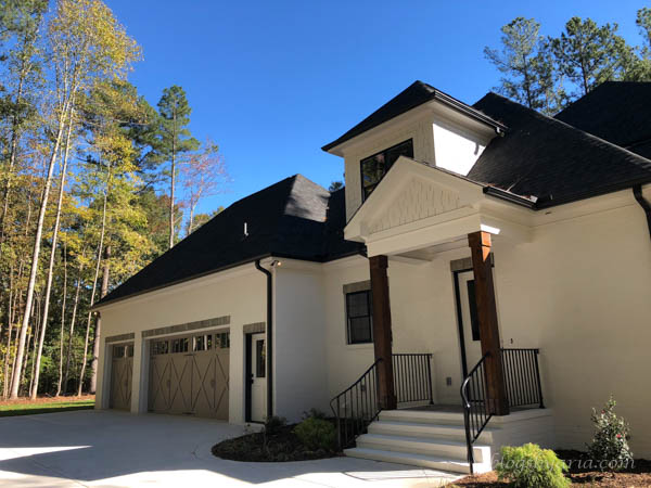 this home is just as beautiful from its side elevation featuring a side door and three car garage
