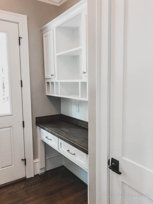 the mudroom also features a built-in desk command center