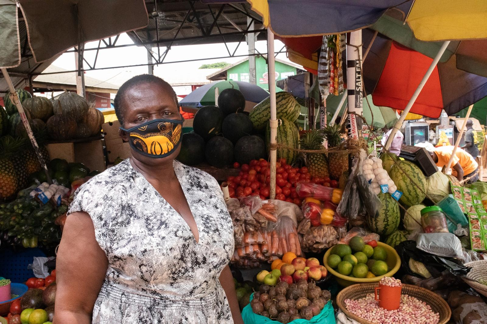 A woman in a face mask by her fruit stall