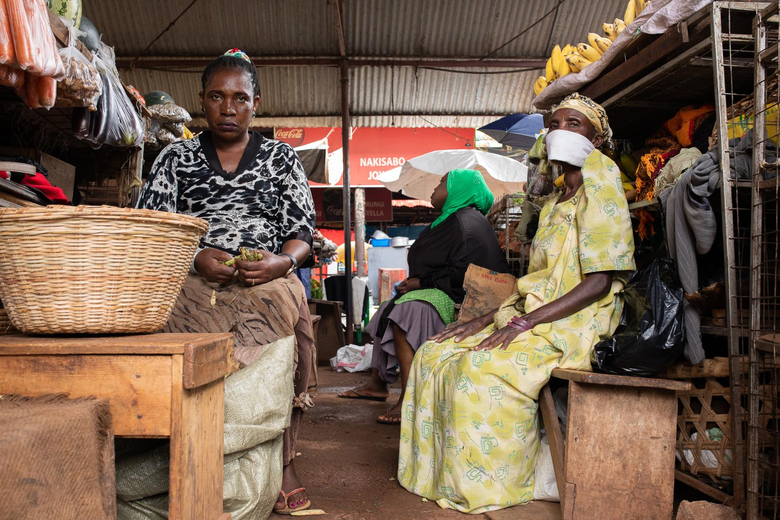 Three women surrounded by good in a market stall