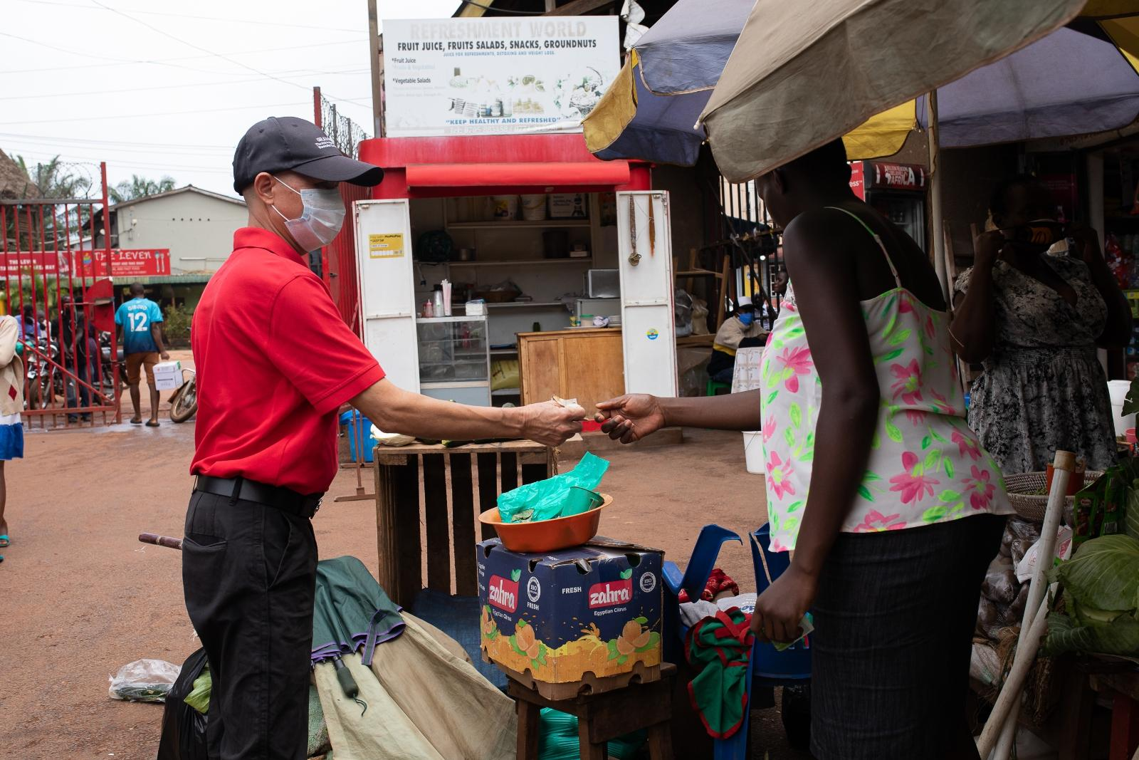 A man buying food from a women outside in Kampala