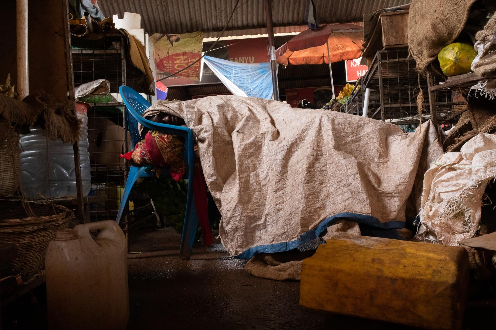A man asleep under a tarpaulin