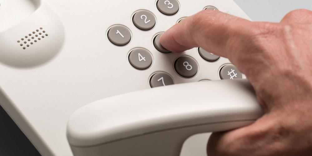Homme qui compose un numéro de téléphone