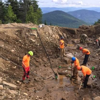 Nettoyage du roc après une forte pluie en préparation de l'installation des ancrages.