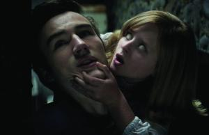 "PARKER MACK as Mikey is attacked by LULU WILSON as Doris in ""Ouija: Origin of Evil.""  Inviting audiences again into the lore of the spirit board, the supernatural thriller tells a terrifying new tale as the follow-up to 2014's sleeper hit that opened at No. 1.  In 1965 Los Angeles, a widowed mother and her two daughters add a new stunt to bolster their séance scam business and unwittingly invite authentic evil into their home.  When the youngest daughter is overtaken by the merciless spirit, this small family confronts unthinkable fears to save her and send her possessor back to the other side."