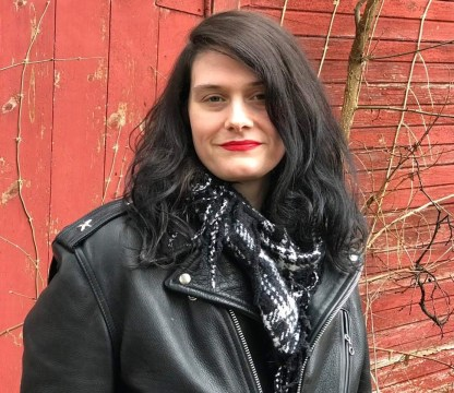 Katie Jean Shinkle in a leather jacket against a red wall. She has long black hair and red lipstick.