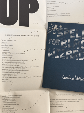 "Photo of the dark blue cover folder next to the oversized unfolded chapbook Spells for Black Wizards by Candace Williams, showing part of the text for a poem called ""On Neoliberalism Or: Why My Black Ass Is Tired."""