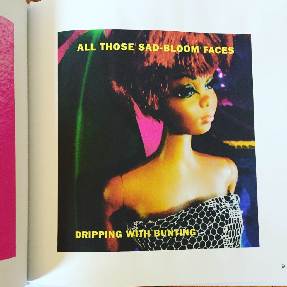 "A book open to page 9 with a color portrait photograph of a black Barbie-style doll in a black strapless dress, in front a a colorful background. The caption in yellow all-caps type says ""Those Sad-Bloof Faces Dripping with Bunting."""