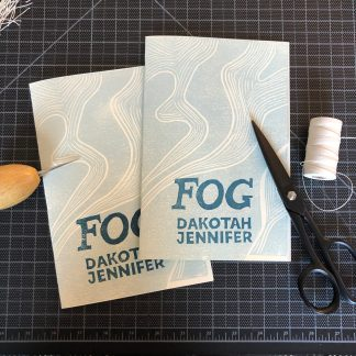 Two copies of Fog by Dakotah Jennifer overlapping on a black gridded cutting mat. The hand-printed linocut cover design consists of white curved lines in a wavelike vertical pattern on a light blue-gray background. Dark blue lettering spells out the title and author name in the lower center. Next to the books are some binding tools: a spool of linen thread, a pair of black scissors, and a wooden-handled awl.