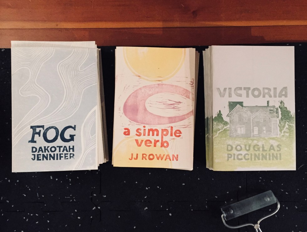 Three chapbooks with linocut covers. From left to right: FOG by Dakotah Jennifer, blue and cream waves with dark blue text; A SIMPLE VERB by JJ Rowan, yellow and lavender geometric shapes with red-orange text; and VICTORIA by Douglas Piccinnini, light green-to-dark green gradient ground with a gray house and gray text.