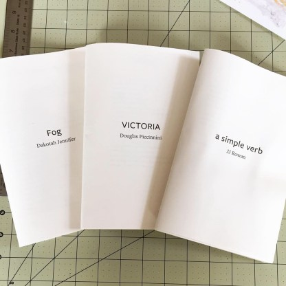 Three folded chapbook interiors, unbound, without covers, black text printed on cream paper. From left to right: Fog by Dakotah Jennifer, Victoria by Douglas Piccinnini, and a simple verb by JJ Rowan.