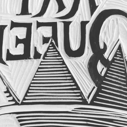 Black and white image, cropped, of the carved linocut block used to print the covers. The word QUEEN and a large crown graphic can be partially seen, with cut lino texture surrounding them.
