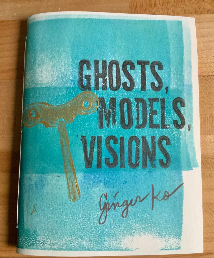 A copy of Ghosts, Models, Visions by Ginger Ko on a maple-top workbench. The hand-printed cover is turquoise blue with brown stamped title, handwritten author name in brown pencil, and a gold stamped windup key. If there is a format you'd find more accessible than PDF, we'd love to hear from you: info@bloofbooks.com