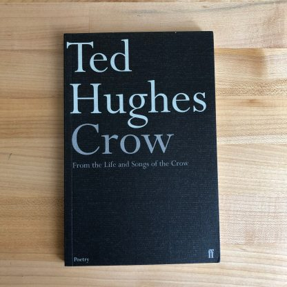 Crow by Ted Huges in paperback, lying on a maple tabletop. The black paperback is covered in textured card with gray lettering and features french flaps.