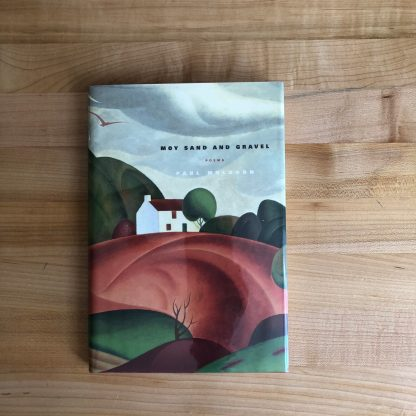 Moy Sand and Gravel by Paul Muldoon. The book is lying flat on a maple table top. The cover painting is of a small white cottage in a landscape.