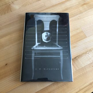 Twenty Questions by J. D. McClatchy in hardcover, lying on a maple tabletop. The book jacket features a black and white photo of a sculpture consisting of a wooden dining chair with a partial face sticking out its tongue affixed in a dark metal box to the seat.