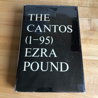 A copy of The Cantos (1–95) by Ezra Pound, lying on a maple tabletop. The black jacket features large white type in the classic New Directions style.