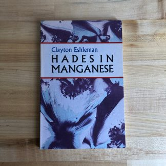 A copy of Hades in Manganese by Clayton Eshleman, lying on a maple tabletop. The paperback cover is printed with an abstract floral pattern in purple and silver on textured paper, in the classic Black Sparrow series style.