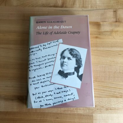 Alone in the Dawn: The Life of Adelaide Crapsey in hardcover, lying on a maple tabletop. The jacket is mauve with two overlapping images: a handwritten page and a photo of Crapsey.