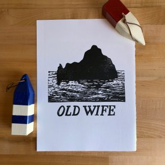 "Old Wife print in 9 x 12 size depicting a silhouetted small rocky island and waves in black in on natural white paper with the words ""Old Wife"" below. Alongside the print on the maple tabletop sit two decorative wooden buoys in red, cream, and blue stripes."