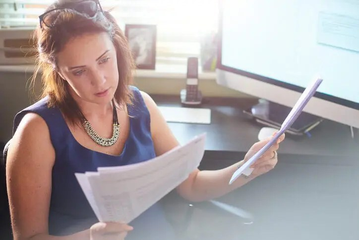 businesswoman reviewing paperwork covering product management vs. project management