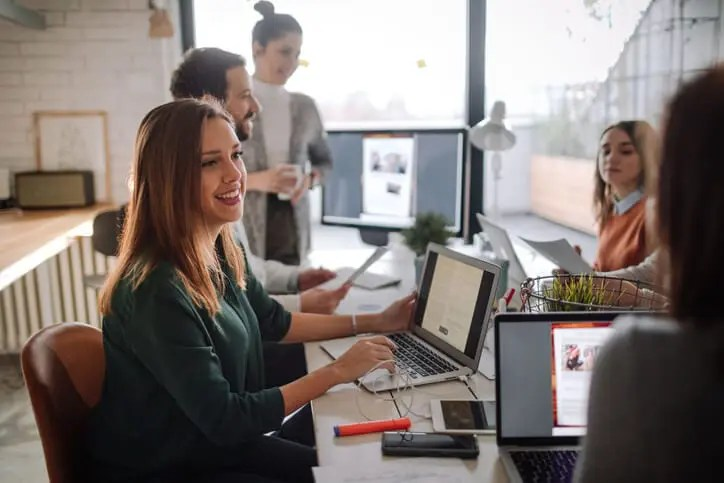 smiling coworkers at shared desk have collisions of ideas