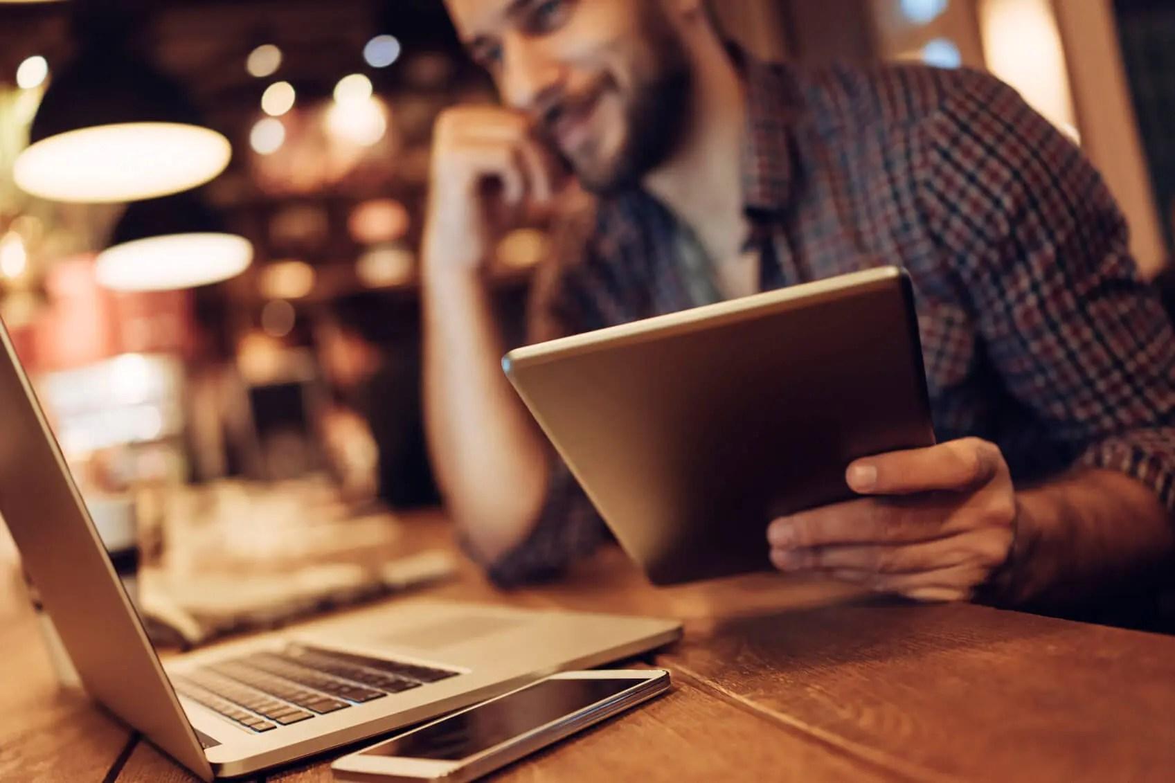 Man using a tablet to provide customer support via social media